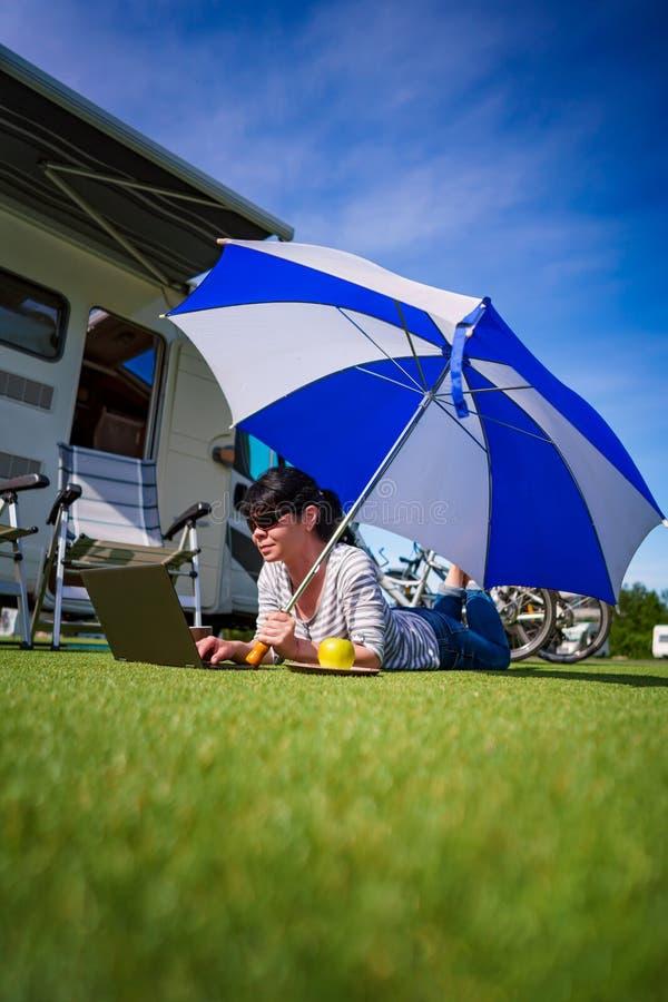 Frau auf dem Gras, den Laptop betrachtend unter Regenschirm nahe Th stockbild