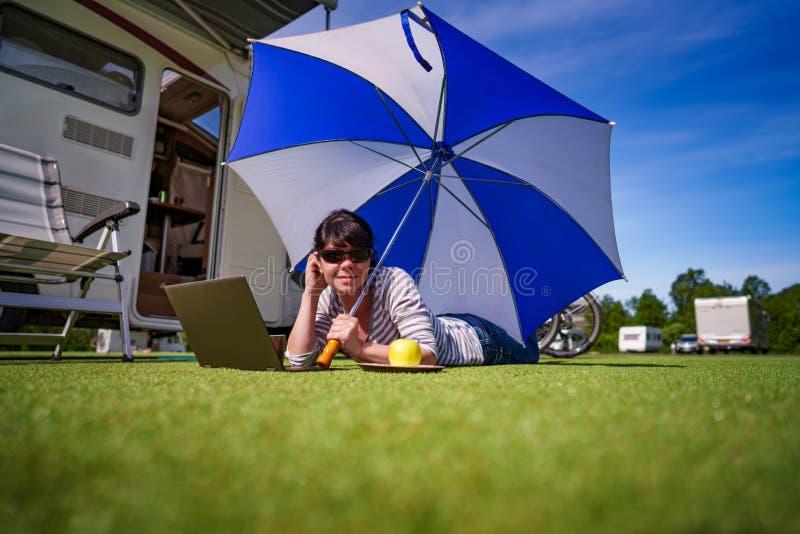 Frau auf dem Gras, den Laptop betrachtend unter Regenschirm nahe Th stockfotografie