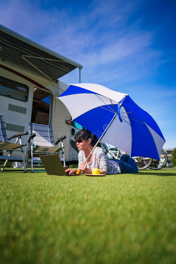 Frau auf dem Gras, den Laptop betrachtend unter Regenschirm nahe Th stockbilder