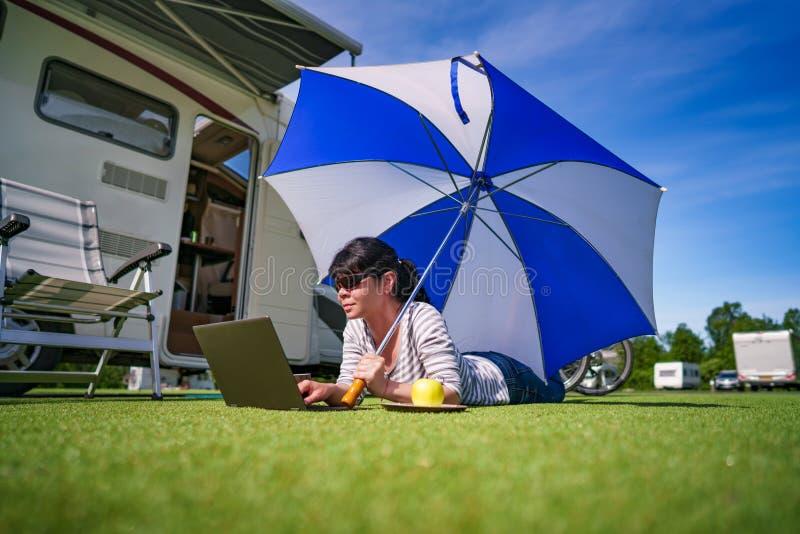 Frau auf dem Gras, den Laptop betrachtend unter Regenschirm nahe Th stockfoto