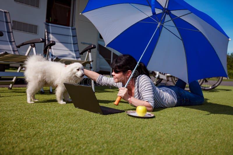 Frau auf dem Gras mit einem Hund, der einen Laptop betrachtet stockbilder