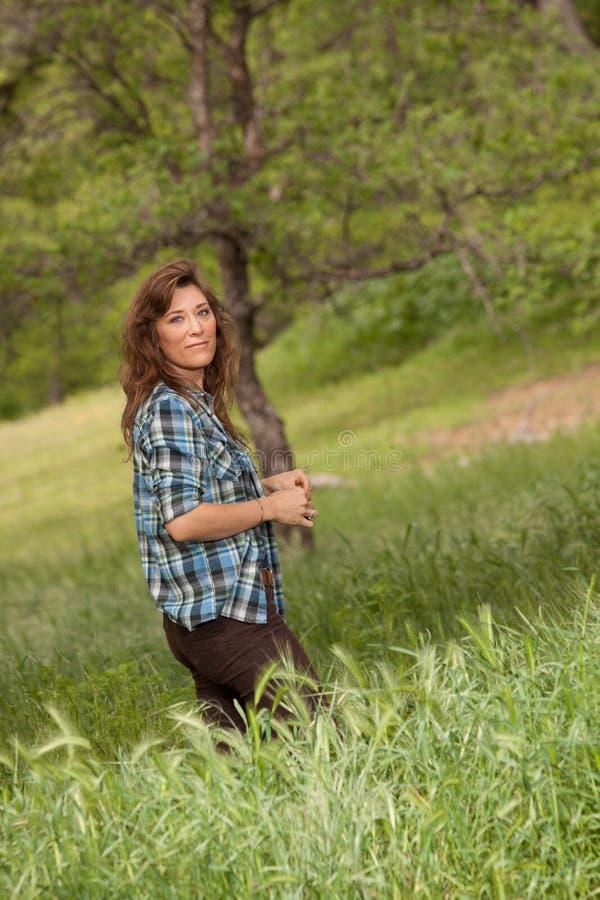 Frau auf dem grasartigen Gebiet, rote Täuschung, CA stockfotografie