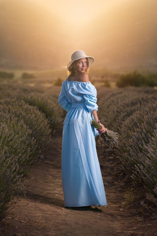 Frau auf dem Lavendel-Gebiet während des Sonnenuntergangs lizenzfreie stockbilder