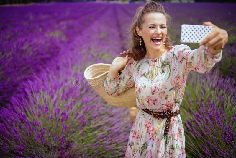 Frau auf dem Lavendelgebiet mit der Strohtasche, die selfie mit Telefon nimmt stockfoto