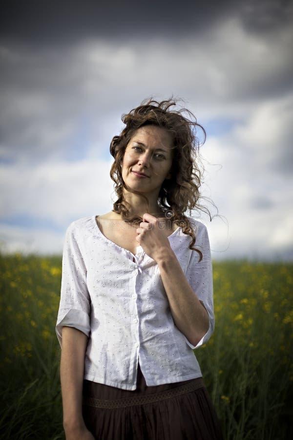 Frau auf dem Rapssamengebiet mit tiefem Blick lizenzfreie stockbilder