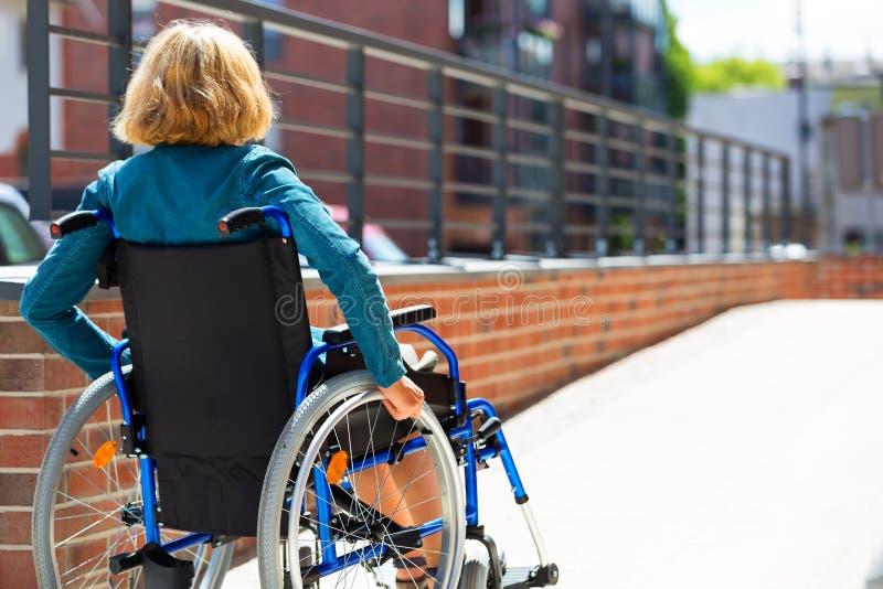 Frau auf dem Rollstuhl, der die Plattform einträgt lizenzfreies stockfoto