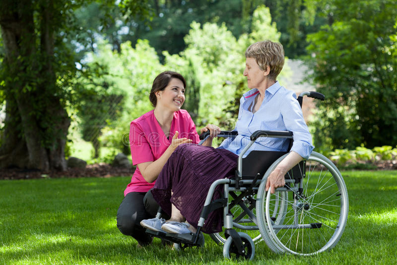 Frau auf dem Rollstuhl, der im Garten sich entspannt lizenzfreie stockfotos
