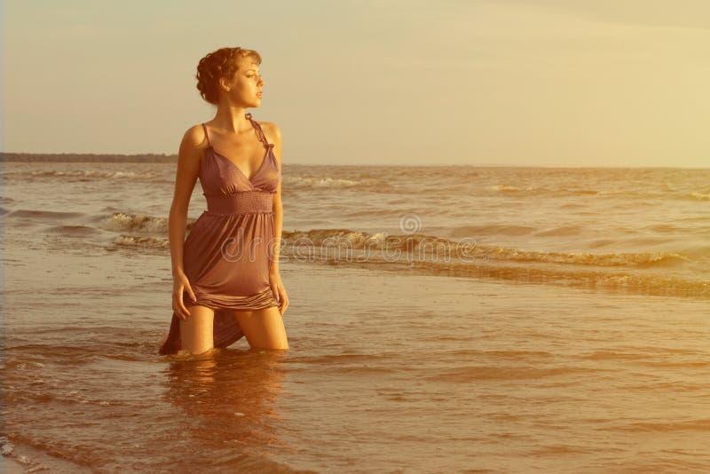 Frau auf dem Strand bei Sonnenuntergang lizenzfreies stockbild
