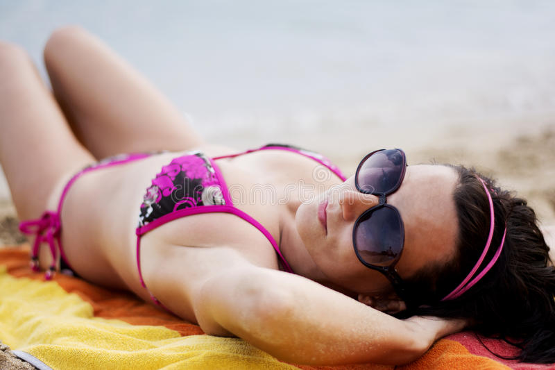 Frau auf dem Strand, der auf Strand legt lizenzfreies stockfoto