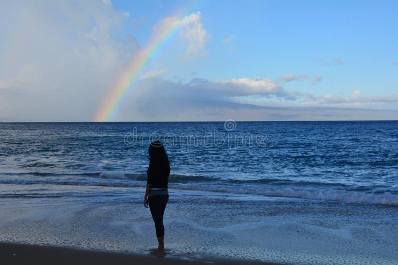 Frau auf dem Strand, der den Regenbogen betrachtet stockfotografie