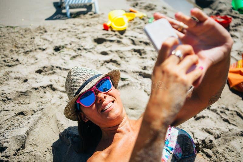 Frau auf dem Strand, der Selbstporträt über Mobile nimmt stockfotografie