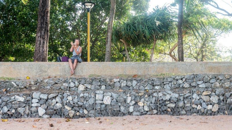 Frau auf dem Strand, der Spiegel untersucht stockbild