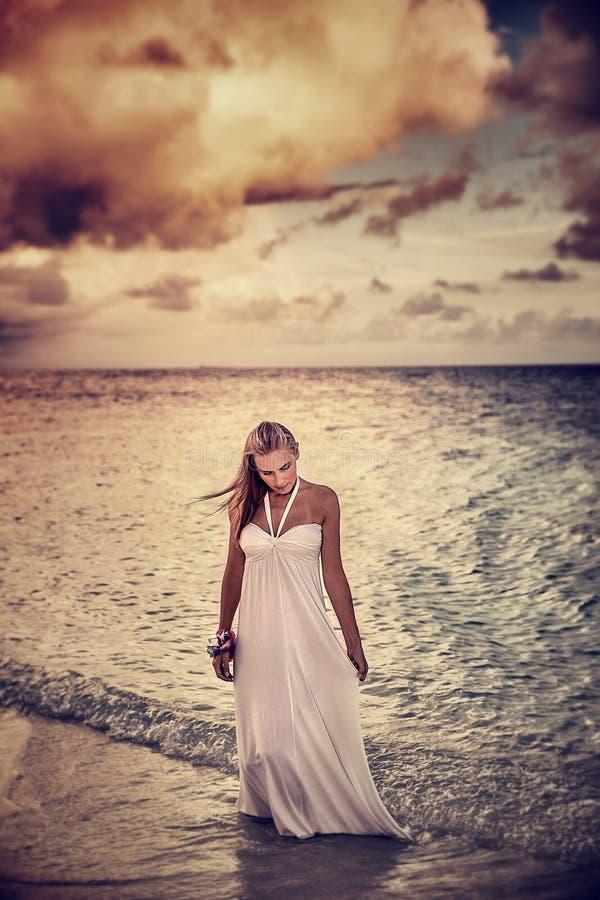 Frau auf dem Strand im bewölkten Wetter lizenzfreie stockfotos