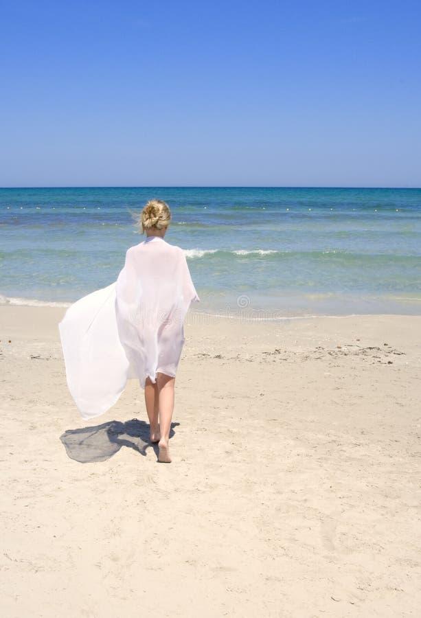 Frau auf dem Strand mit einem weißen Sarong lizenzfreie stockfotografie
