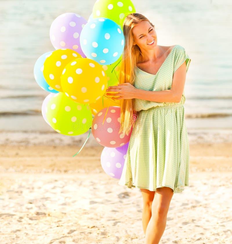 Frau auf dem Strand mit farbigen Tupfen steigt im Ballon auf lizenzfreies stockfoto