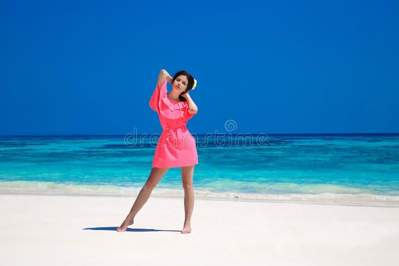 Frau auf dem Strand Schönes dünnes Mädchenmodell im roten Kleid-resti lizenzfreie stockfotografie