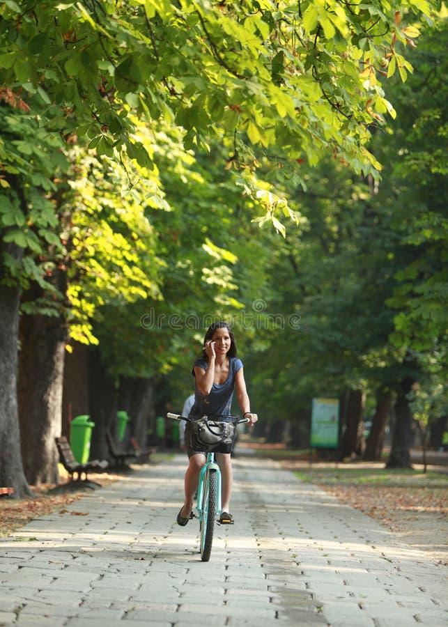 Frau auf dem Telefonreitfahrrad lizenzfreies stockfoto