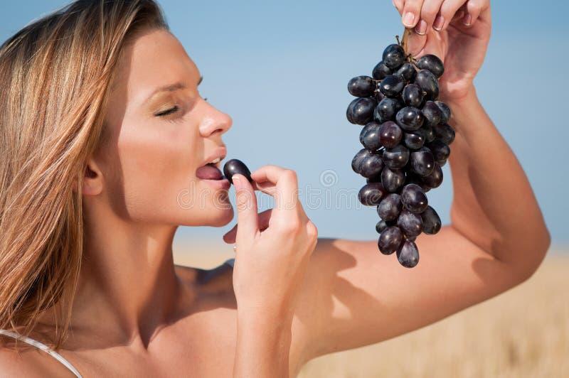 Frau auf dem Weizengebiet Trauben essend. Sommerpicknick. stockbilder