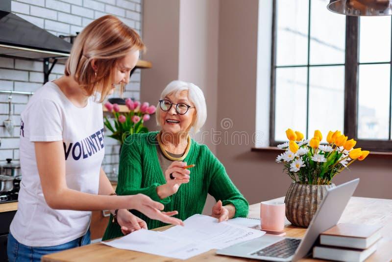 Frau auf der Pension, die Gespräch über Dokumente mit Sozialangestelltem hat stockfoto