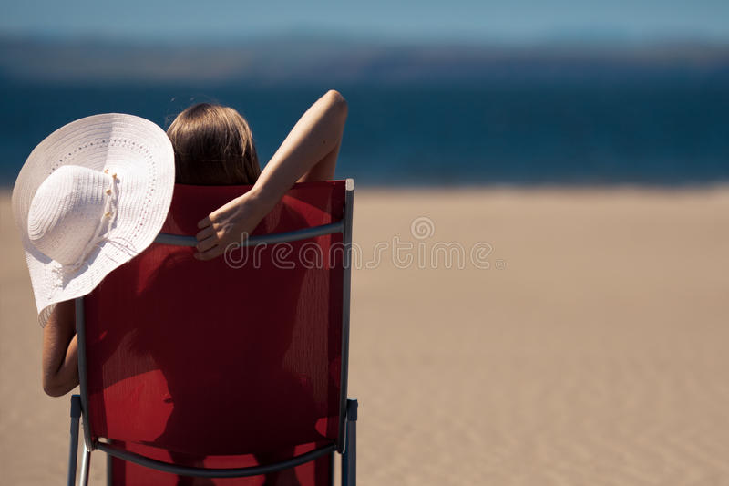 Frau auf einem deckchair am Strand stockfotografie