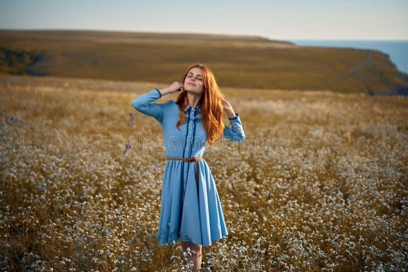 Frau auf einem Gebiet von Blumen stockfotografie