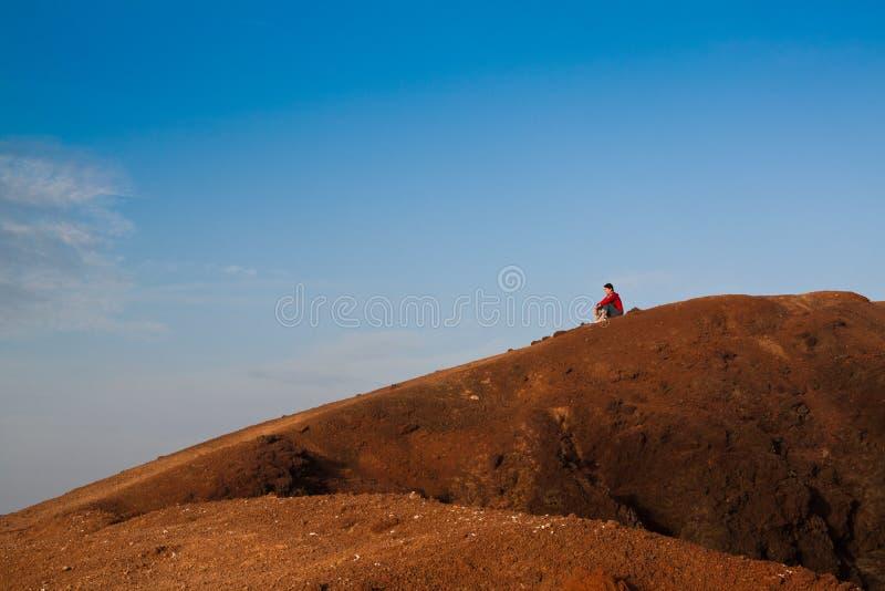 Frau auf einem Hügel, der unten schaut stockfotos
