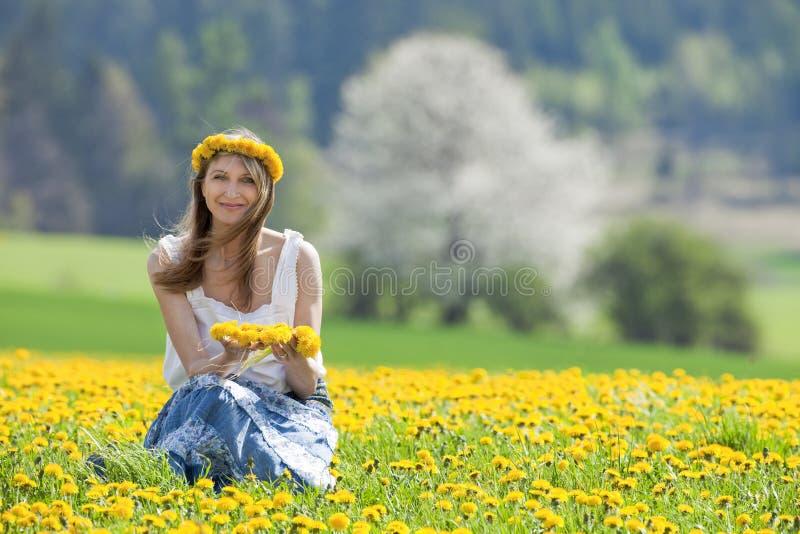 Frau auf einem Löwenzahngebiet lizenzfreies stockfoto