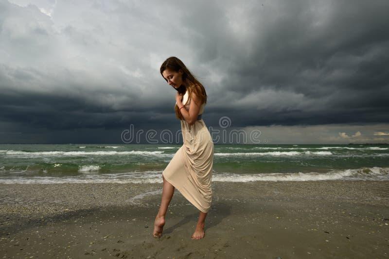 Frau auf einem Strand bei dem Sonnenuntergang lizenzfreies stockfoto