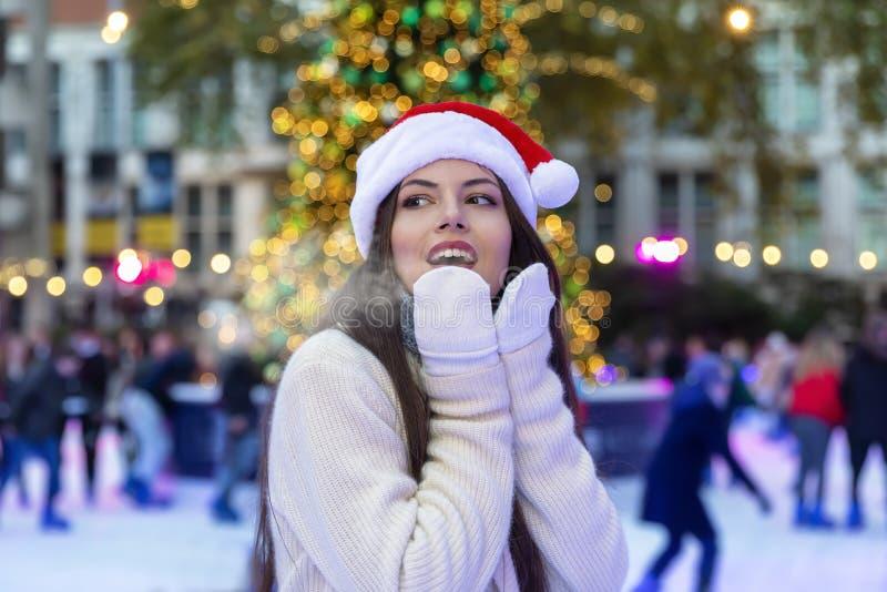 Frau auf einer Eisbahn auf einem Weihnachtsmarkt lizenzfreie stockbilder