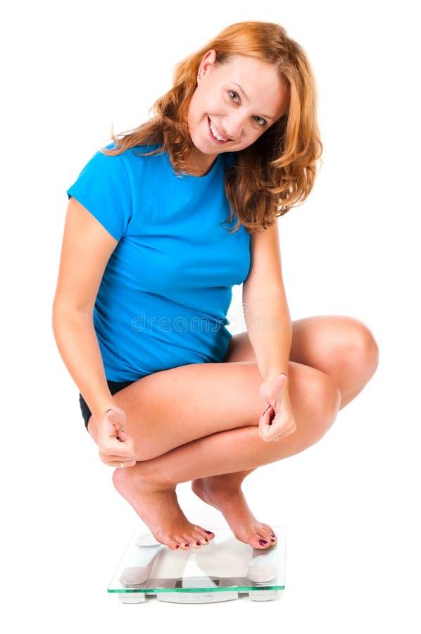 Frau auf Gewichtskala lizenzfreie stockfotos