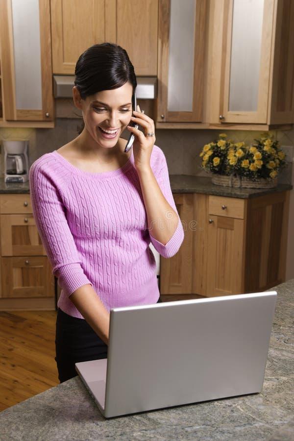 Frau auf Handy mit Laptop stockfotos