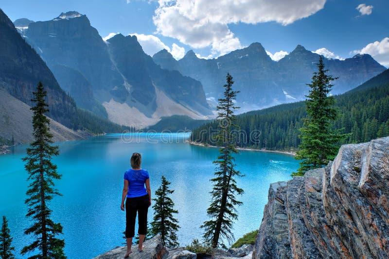 Frau auf Klippe am szenischen See und an den Bergen stockfoto