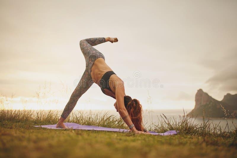 Frau auf Klippe in Yogaposition stockbild