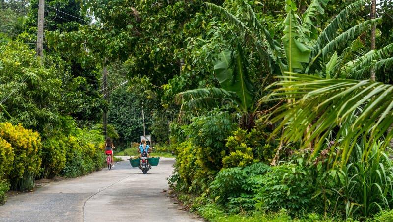 Frau auf Motorrad und Mädchen auf Fahrrad lizenzfreie stockfotografie