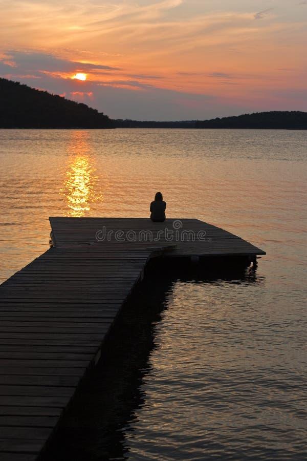 Frau auf Pier mit Sonnenuntergang stockbilder