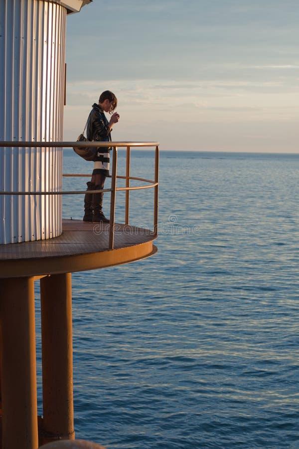 Frau auf Plattform durch Meer lizenzfreie stockbilder