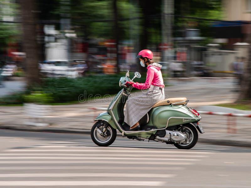 Frau auf Roller in Ho Chi Minh City lizenzfreies stockfoto