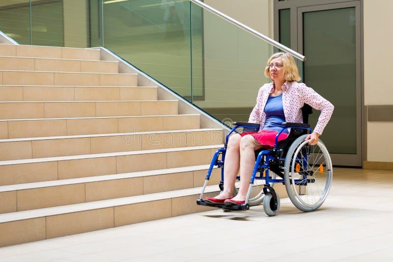 Frau auf Rollstuhl und Treppe lizenzfreie stockbilder