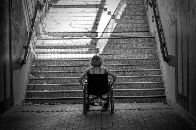Frau auf Rollstuhl und Treppe stockbild