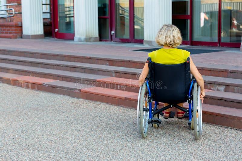 Frau auf Rollstuhl und Treppe lizenzfreies stockbild