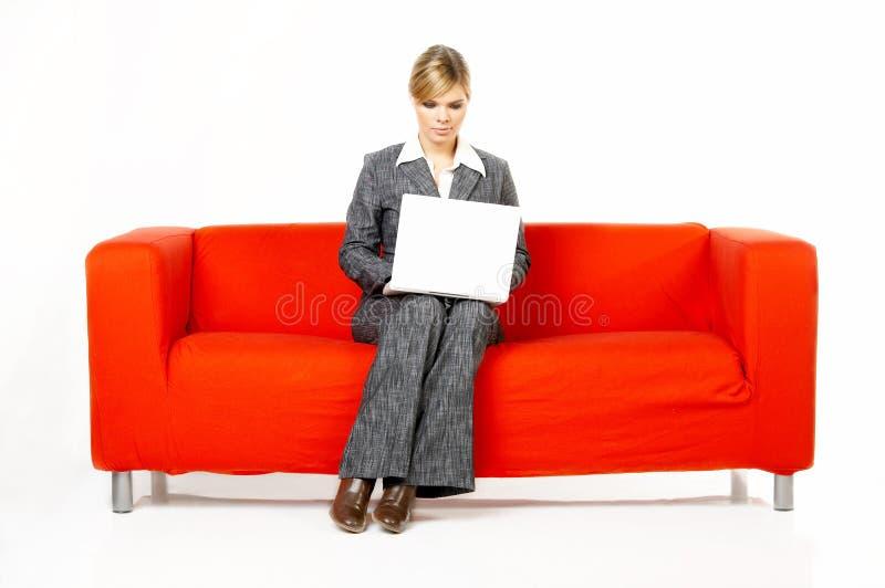 Frau auf roter Couch lizenzfreies stockfoto