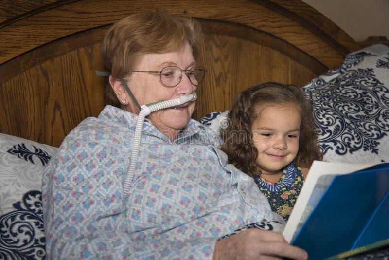 Frau auf Sauerstoff liest zum Kind lizenzfreie stockfotografie
