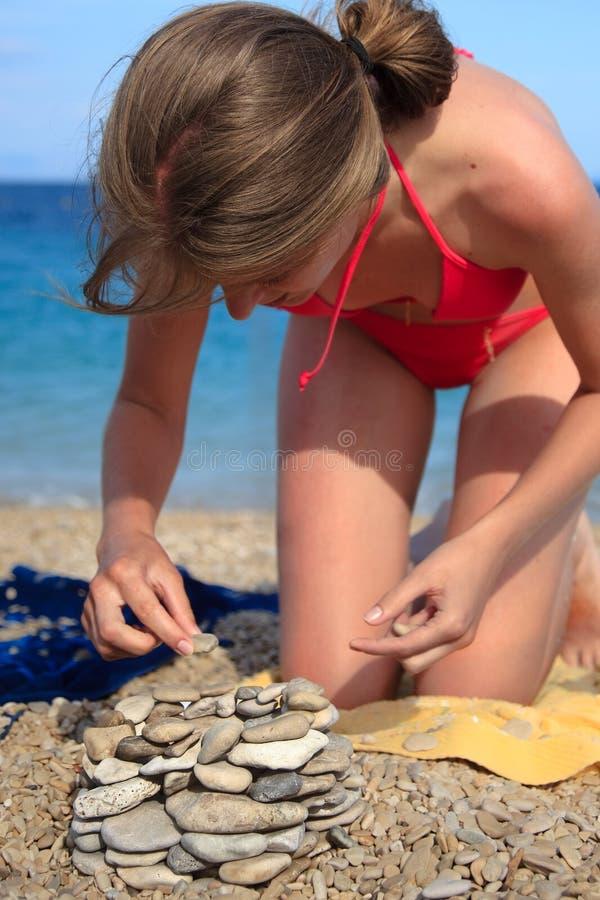 Frau auf Strand baut Haus aus Kieseln heraus auf stockfoto