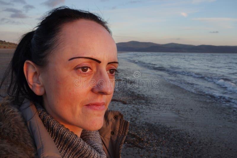 Frau auf Strand bei Sonnenuntergang stockfotografie