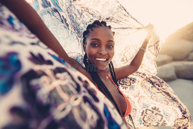 Frau auf Strand mit Schal in der Brise lizenzfreie stockfotos