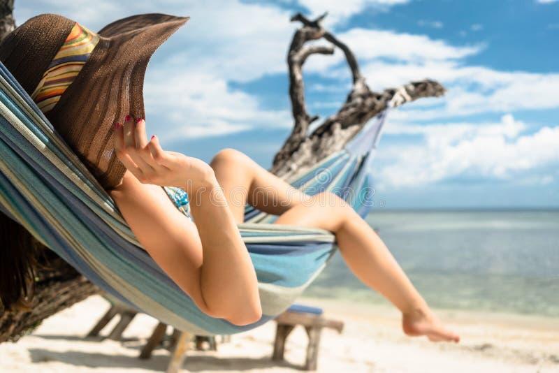 Frau auf Strandferien in der Hängematte durch Meer stockfotografie