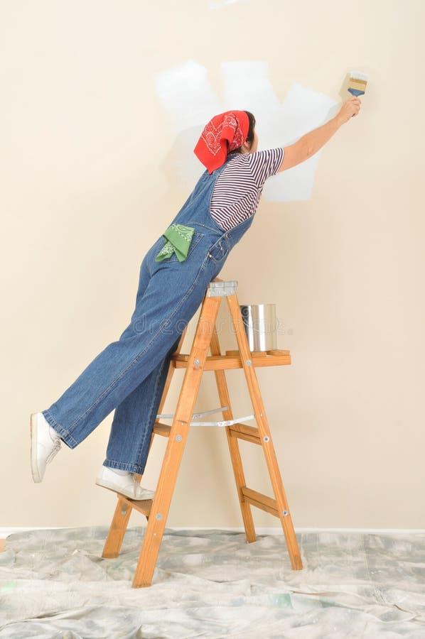 Frau auf Strichleiter-Anstrich lizenzfreies stockfoto