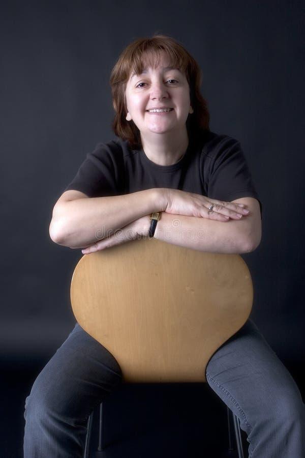 Frau auf Stuhl lizenzfreie stockfotografie