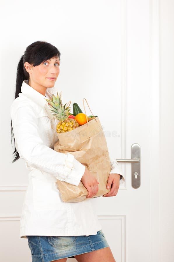Frau auf Tür mit Nahrungsmittelkauf stockfotografie