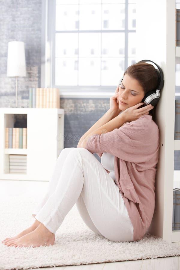 Frau auf Wohnzimmerfußboden mit Kopfhörer stockfoto
